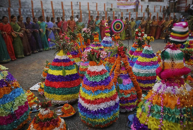 Hindu women dance around Bathukammas, floral arrangement representing the giver of life, during the Bathukamma festival dedicated to the Hindu goddess Gauri, in Hyderabad, India, Tuesday, Oct. 4, 2011. (AP Photo/Mahesh Kumar A.)